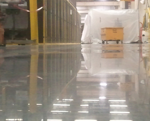 Floor polishing at automotive manufacturing company.